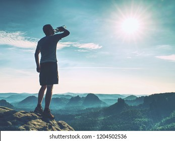 Sportsman drinking water in nature. Sweaty tired man drink water after jogging in outdoor.