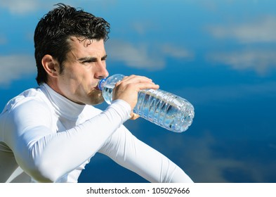 Sportsman drinking. Young male athlete drinking from water bottle after training. Copy space.