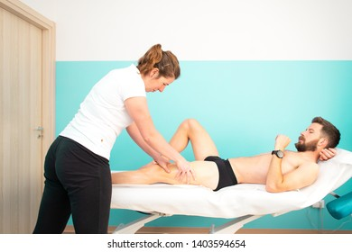 A sportsman during a masseur and physiotherapist treatment at the quadriceps