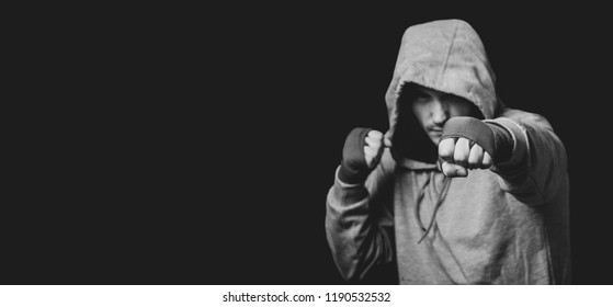 Sportsman fighter boxer in a hood punching in the dark. Portrait with copy space.