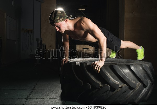 Sportsman. Fit sporty man doing push ups on tire strength power training concept crossfit fitness workout sport and lifestyle