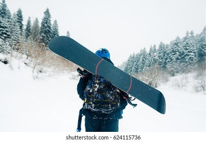sportsman go with snowboard equipment on the snow hill with green forest