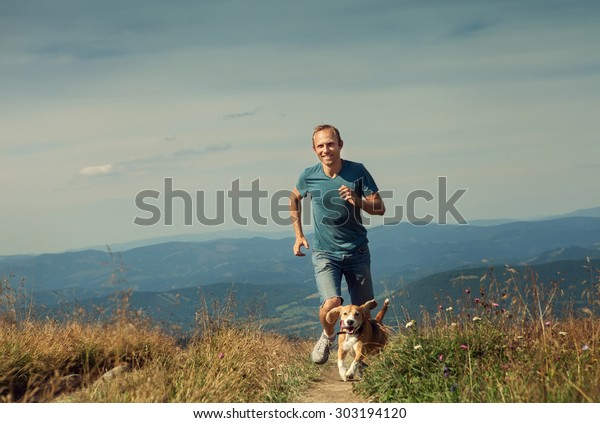 Sportsman has a mountain jogging walk with his beagle dog