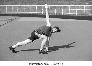 sportsman. healthy lifestyle and workout, athletic bearded man or sexy handsome guy with muscular body doing exercises on stadium sunny outdoor in blue sportswear, summer activity and sport