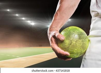 Sportsman holding a ball against handball field indoor