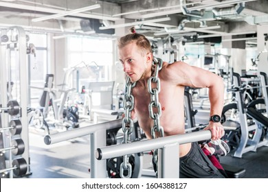 Sportsman with a huge metal chain around his neck. Push-ups on the uneven bars in the gym