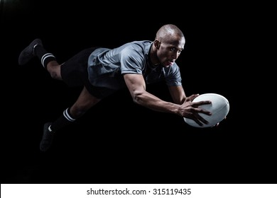 Sportsman jumping for catching rugby ball over black background