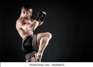 Sportsman kick boxer fighting against black background.