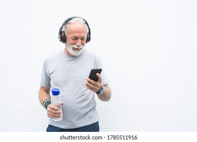 Sportsman listening music using mobile phone and headphones