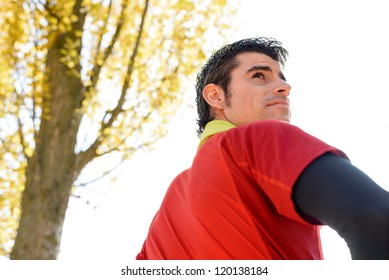 Sportsman looking over shoulder outdoor. Male athlete portrait with towel around neck. Caucasian handsome man.