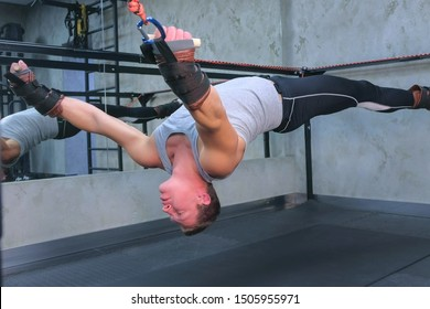 Sportsman making exercises for spine using trainer for myofascial stretching in gym raising in air. Recovery exercises rehabilitation after trauma musculoskeletal system. Professional sport equipment.