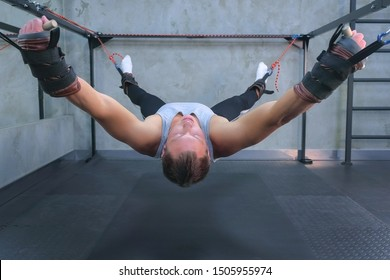 Sportsman making exercises using trainer for myofascial stretching in gym raising in air. Recovery exercises rehabilitation after trauma musculoskeletal system. Professional sport equipment.