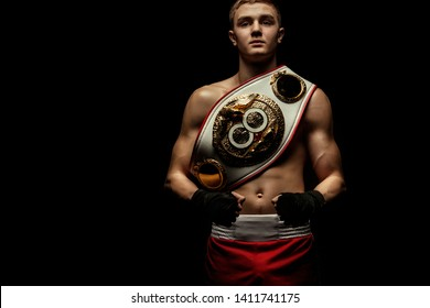 Sportsman, man boxer fighting in gloves with a championship belt. Isolated on black background. Copy Space.