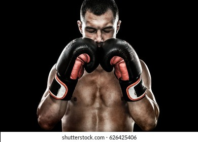 Sportsman Muay Thai boxer celebrating flawless victory in boxing cage. Isolated on black background with smoke. Copy Space.