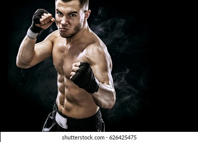 Sportsman muay thai boxer fighting in boxing cage. Isolated on black background with smoke. Copy Space.