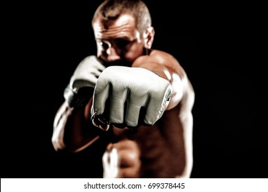 Sportsman muay thai boxer fighting in boxing cage. Isolated on black background. Box trainer on ring hitting