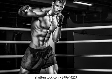 Sportsman muay thai boxer fighting in boxing cage. With copy Space. Black and white photo. Sport concept.