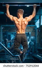 sportsman with muscular torso exercising; young bodybuilder with perfect body pull up with gym bar;