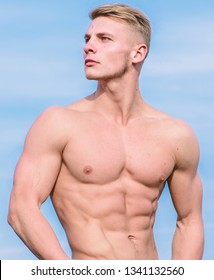 Sportsman muscular torso posing. Man muscular torso stand confidently. Sport and bodycare. Muscular masculine guy look confident. Man sexy muscular bare torso stand outdoor blue sky background.