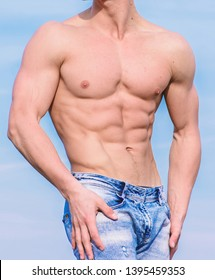 Sportsman muscular torso posing. Sport and bodycare. Muscular masculine guy look confident. Man sexy muscular bare torso stand outdoor blue sky background. Man muscular torso stand confidently.