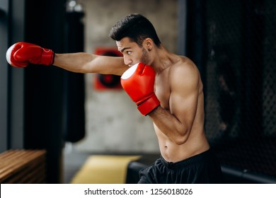Sportsman with a naked torso and the red boxing gloves on his hands stands hits with right hand in the boxing gym