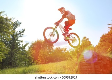Sportsman on a mountain bike is flying in a jump from a springboard with special ligth lens effect