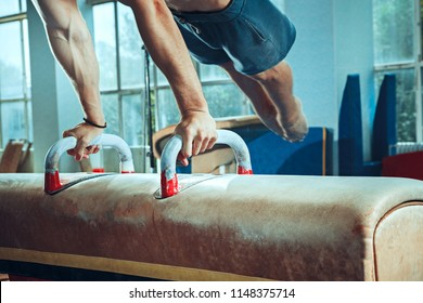 The sportsman performing difficult gymnastic exercise at gym. The sport, exercise, gymnast, health, training, athlete concept. Caucasian fit model