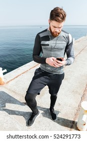 Sportsman with phone near the sea. full length image. looking at phone