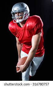 Sportsman playing American football against black background