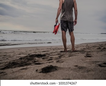 sportsman RECOVERING after crossfit workout barefoot at the beach holding his shoes