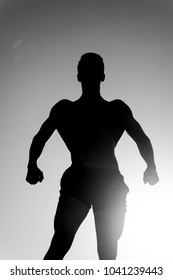 Sportsman relaxing muscles, biceps, triceps outdoors. Bodybuilder posing on sky and sun light background. Silhouette of strong man. Athlete showing muscular body in dusk. Fitness and sport concept.