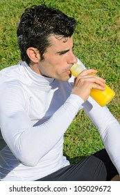 Sportsman resting and drinking  to recover sugar , mineral salts and energy with an isotonic drink.