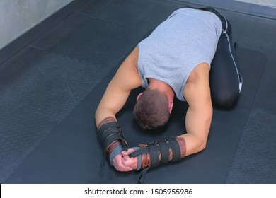 Sportsman resting on mat after using trainer for myofascial stretching in gym. Recovery exercises for rehabilitation after trauma musculoskeletal system. Professional sport equipment. Looks at camera.