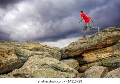 Sportsman running, jumping over rocks in mountain area.
