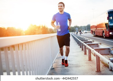 Sportsman running over bridge during sunset