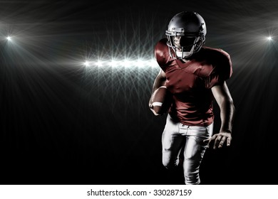 Sportsman running while playing American football against spotlight