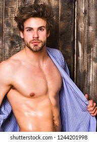 Sportsman show six pack sexy torso. Bachelor sexy body chest and belly. Guy shimmering skin undressing bathrobe. Sexy attractive macho tousled hair on wooden background. Man athlete with fit torso.