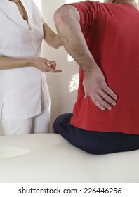 Sportsman sitting on couch clutching lower back with left hand indicating a back injury seeking advice from female health specialist