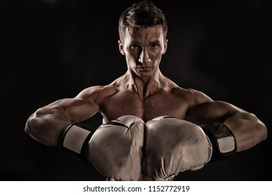 Sportsman with stern look isolated on black background. Man with muscular body wearing boxing gloves. Athlete at training, strength and self discipline concept. Man with strong spirit working out.