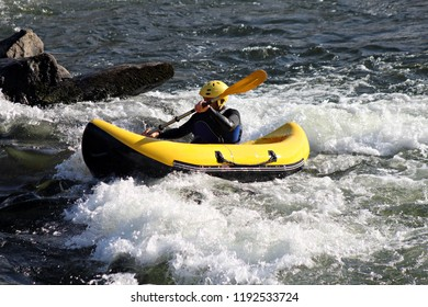 A sportsman surfs the rapids of a river in his canoraft having fun with the adrenaline to butt, during a sunny spring day
