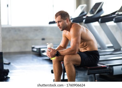 sportsman  taking a break after running on treadmill machine at the gym sitting  and drinking gatorade water at sport club. Fitness Healthy lifestye and workout at gym concept.