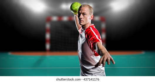 Sportsman throwing a ball against handball field indoor