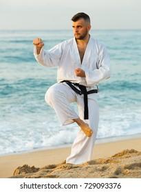 Sportsman is training kick on the beach near the sea.