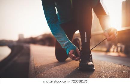 Sportsman tying shoelaces after jogging exercises