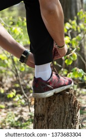 Sportsman tying sneakers in forest