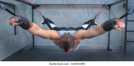 Sportsman is using myofascial stretching trainer in gym, rising tied hands and feet. Recovery exercises for rehabilitation after trauma of musculoskeletal system. Professional sport equipment.