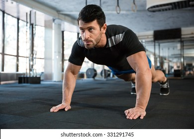 Sportsman wearing blue shorts and black t-shirt doing push-ups