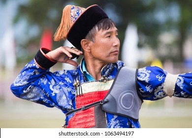 """The sportsman wears a traditional Buryat-Mongolian suit, shooting arrows during the national holiday of the Buryat """"Sagalgan"""" in the countryside of Siberia."""