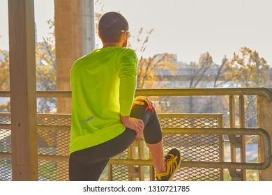 Sportsman working out / jogging on a big city urban bridge.