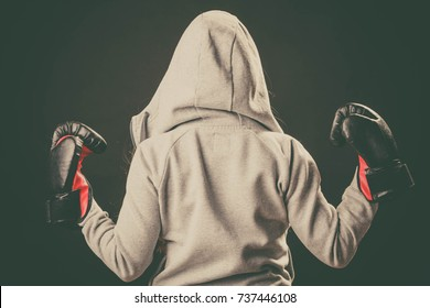 Sportsmanship and strong body. Win fight with opponent. Young woman wear hoodie victory pose show emotion with arms in air. Girl wear boxing gloves.